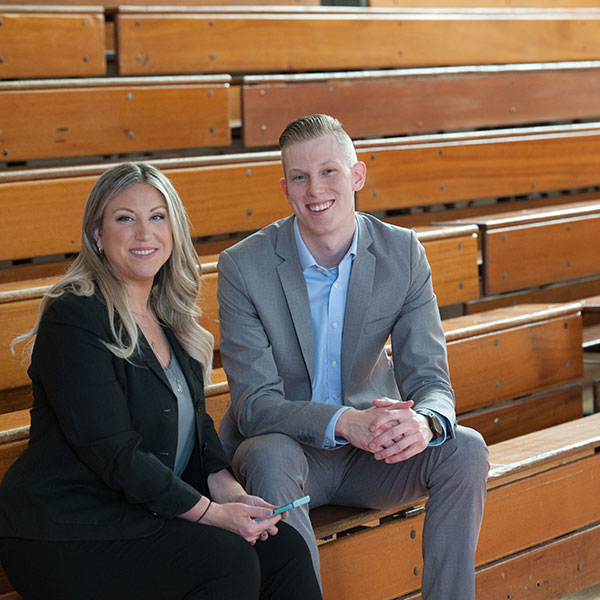 Phaedra and Ben sit on school bleachers, prepping for a client event